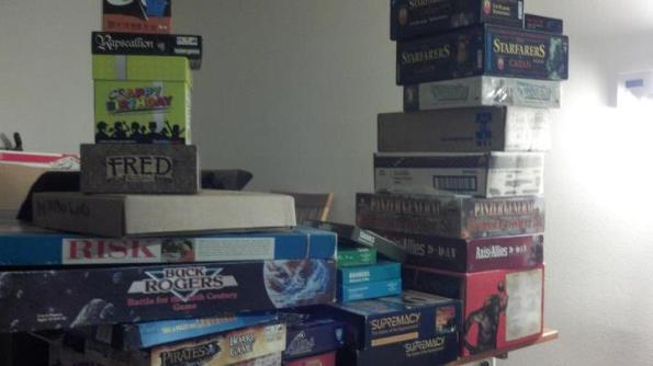 Stacks of board games on a table.